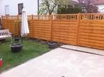Terrasse aus Betonplatten und Sichtschutzzaun aus Holz